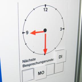 Uhrzeitanzeige hängt an einem Whiteboard und zeigt die Uhrzeit halb neun