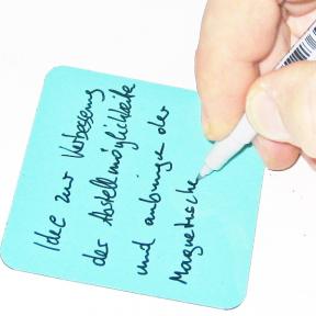 Haftnotiz Magnet wird mit Hand beschrieben