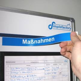Mit Hand wird Überschriftmagnet einfach an das Whiteboard aufgebracht