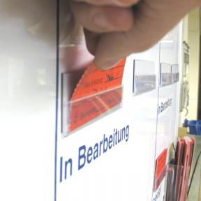 Die Mängelkarte wird von Hand in den Kartenhalter Mag S gesteckt