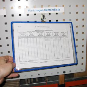 Die Hängesichttafel A4 Q mit farbigem Rahmen ist an einer Lochwand am Haken befestigt