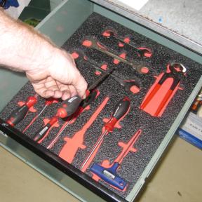 Hand nimmt Werkzeug aus Schublade