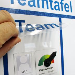 Aufkleben eines Etiketts auf Teamtafel