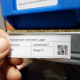 Kanbanbogenetikett 71x25 G wird mit Hand auf Regalboden geklebt