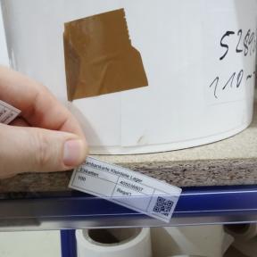 Kanbankarte Falt 71x25 G wird von Hand in eine Steckschiene eingesteckt