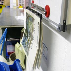 Mit dem Handbuchhalter A4 wird eine Arbeitsanweisungen an einem Whiteboard befestigt