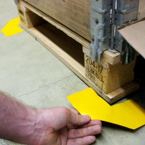 Die B-Ecken Grip 100 werden mit Hand auf den Hallenboden am Palettenplatz geklebt