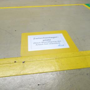 B-Sign C A4 wird mit Ausdruck auf den Boden in der Stellfläche geklebt